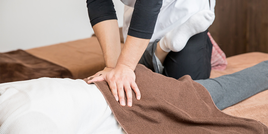 患者の腰を施術する男性