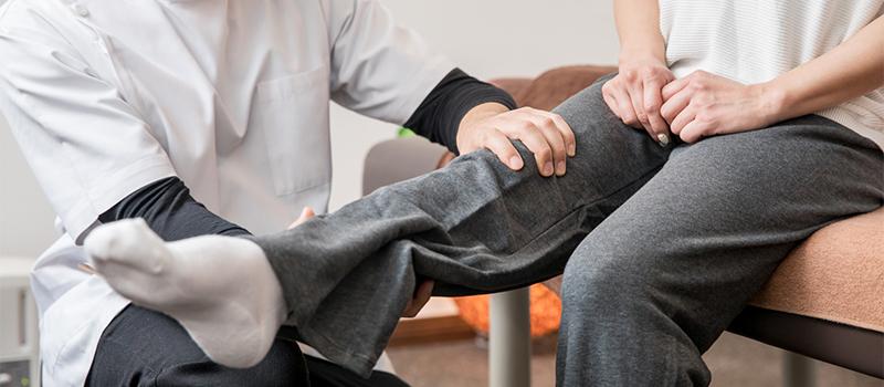 患者の膝をチェックする男性