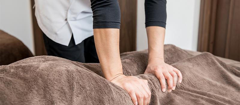 患者の膝付近を揉みほぐす男性